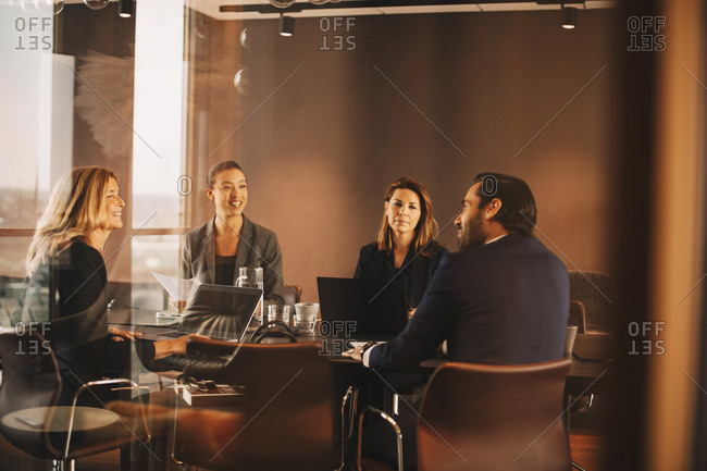 Male and female advisors discussing at conference table in office meeting