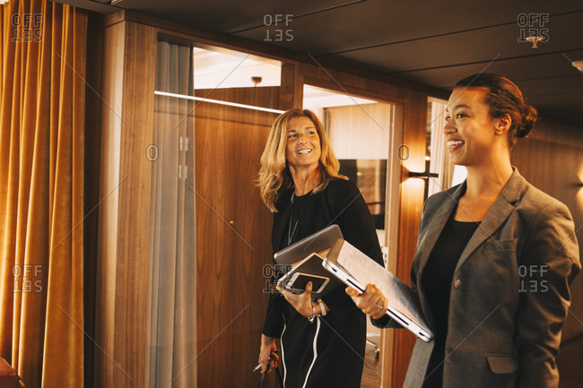 Smiling female lawyers with files discussing in corridor at office