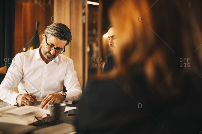 Mature lawyer signing documents during meeting at law office