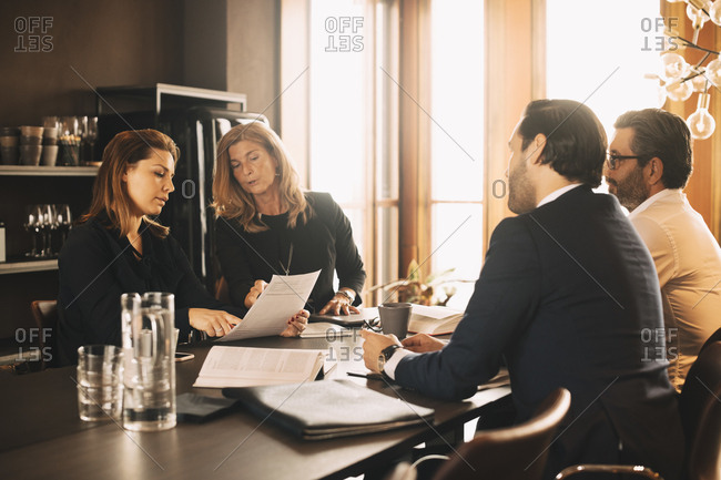 Lawyers discussing over evidence in meeting at office