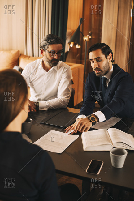 High angle view of mid adult lawyer discussing over documents with colleagues in meeting at office