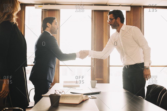 Businessman shaking hands with male lawyer after meeting in board room