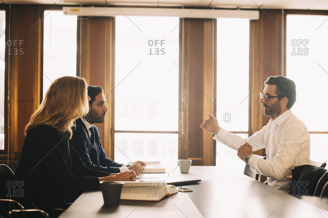 Businessman explaining problems to lawyers in meeting at office