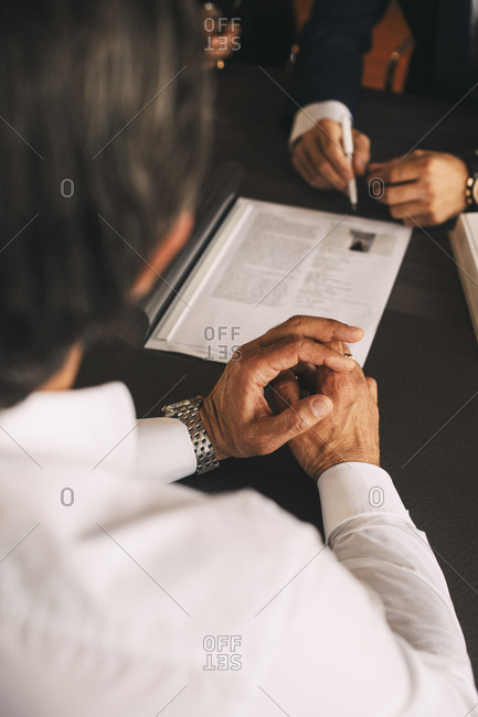High angle view of businessman discussing over document in meeting at office