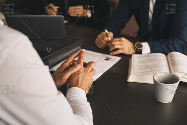 Midsection of lawyer with client in meeting at law office