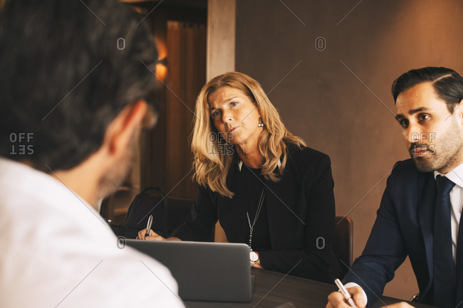 Serious legal coworkers listening to mature businessman during meeting at law office