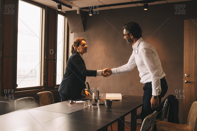 Mid adult lawyer shaking hands with mature client at board room in law office