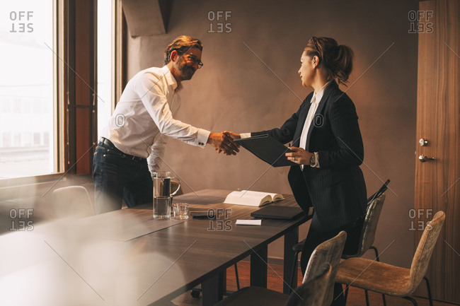 Female lawyer shaking hands with male customer after meeting at table in office