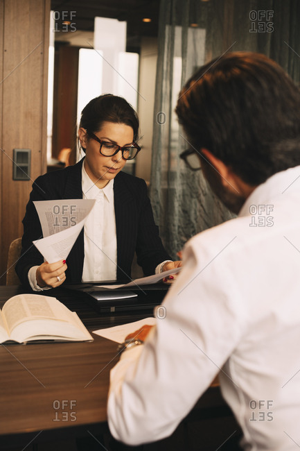 Female financial advisor reviewing documents while sitting with customer in meeting at office
