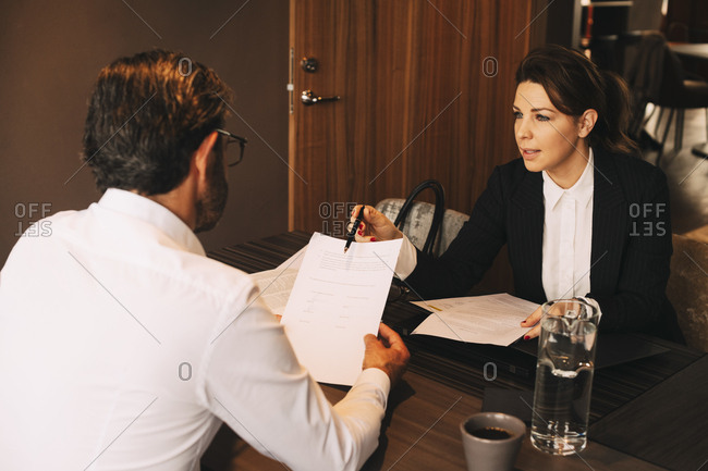Mid adult lawyer explaining documents to mature client in meeting at law office