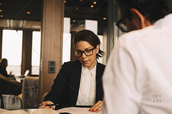 Mid adult female lawyer discussing paperwork with client at table in office
