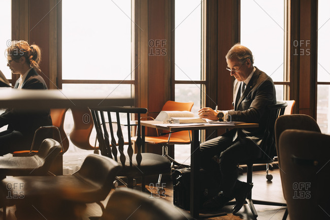 Lawyer studying evidences at table in office