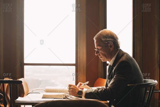 Side view of mature lawyer researching while reading books at office