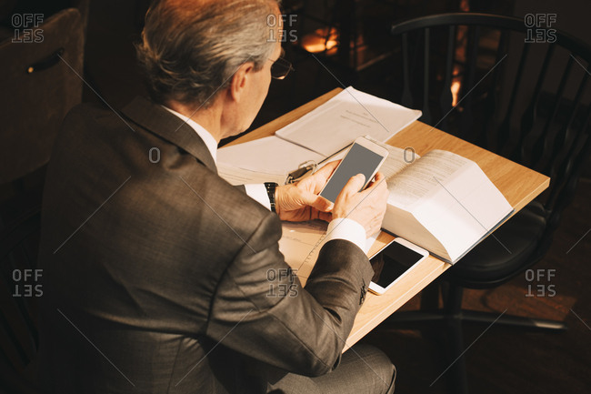 High angle view of male lawyer using smart phone while working at law office