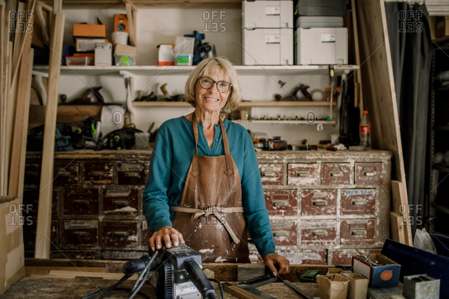 Portrait of smiling senior female entrepreneur standing at workshop