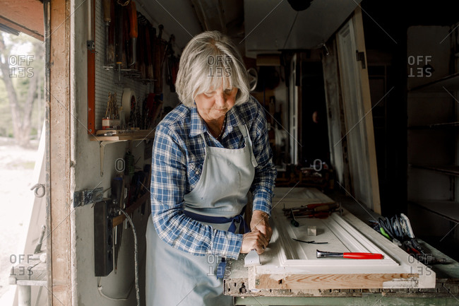 Confident senior female owner scraping on window frame at store workshop