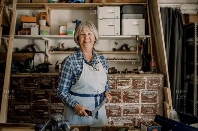 Portrait of confident senior female entrepreneur holding set square at workshop