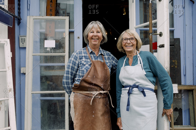 Portrait of cheerful senior female coworkers standing at store entrance