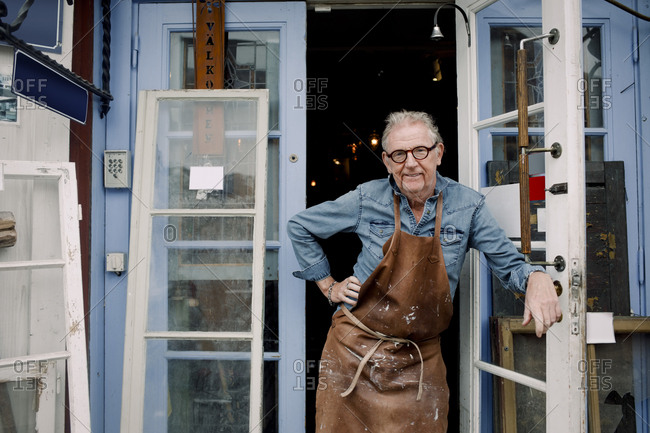 Portrait of senior hardware store owner standing with hand on hip while leaning on door