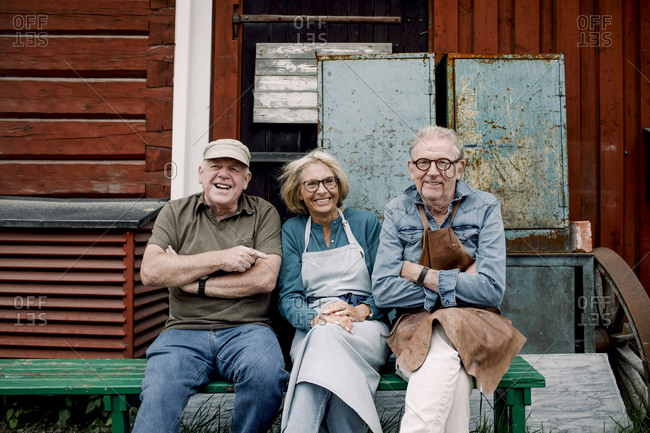 Portrait of smiling senior coworkers sitting on bench against hardware store
