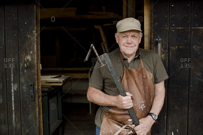 Portrait of confident senior male owner holding equipment while standing at store entrance