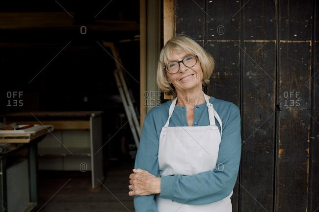 Portrait of smiling senior entrepreneur standing at hardware store entrance