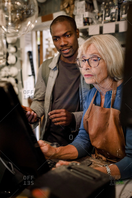 Male customer and senior saleswoman discussing over computer at checkout in hardware store