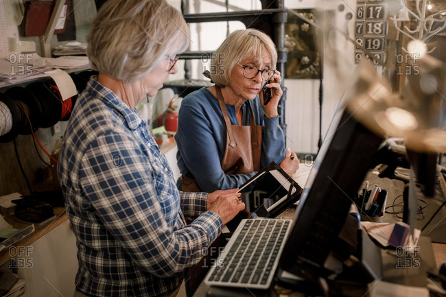 Senior female coworkers working at checkout in hardware store