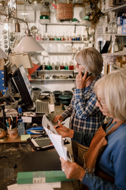 Senior female owner reading documents by coworker talking on mobile phone at checkout in store