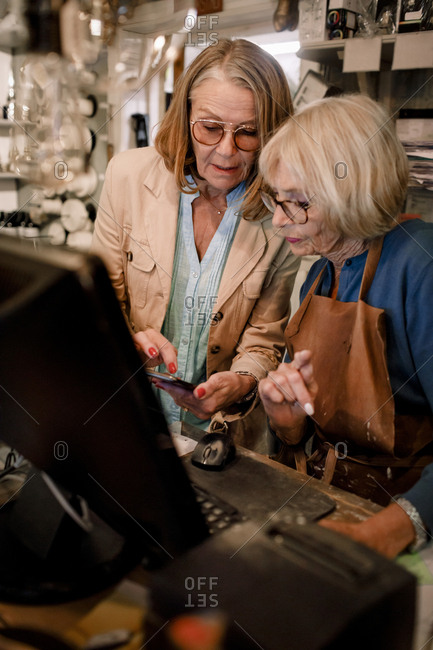 Senior female customer showing smart phone while standing by saleswoman at checkout in hardware store