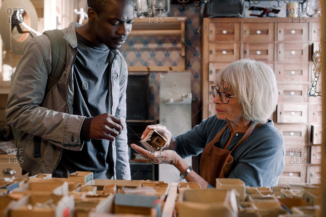 Senior saleswoman assisting male customer with nails at hardware store