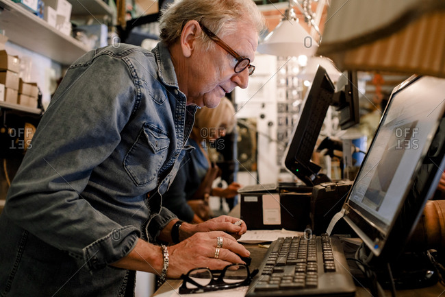 Side view of confident salesman in denim shirt using computer at hardware store checkout