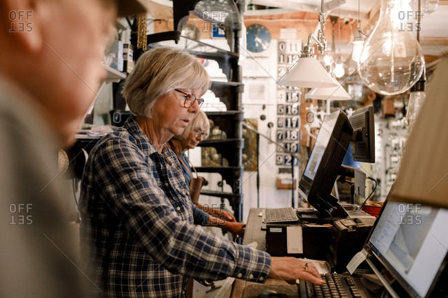 Confident senior female owner using computer while standing amidst coworkers at checkout in illuminated hardware store