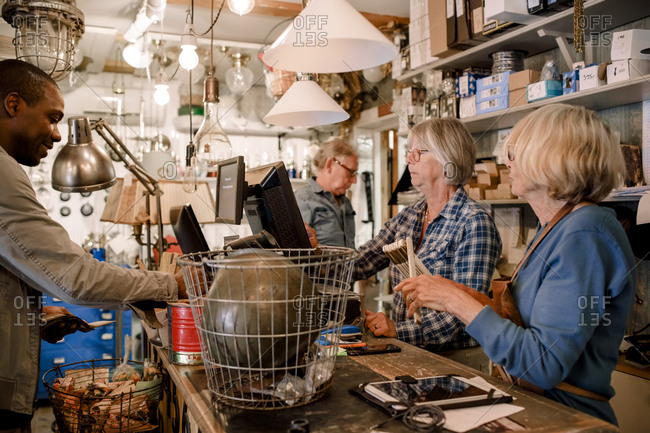 Male customer standing with female owners at checkout in hardware store