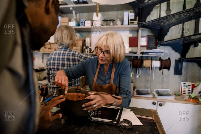 Senior saleswoman explaining leather purse to male customer at checkout in store