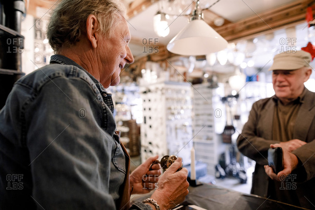 Smiling senior male sales clerk talking with customer while holding equipment at checkout in hardware store