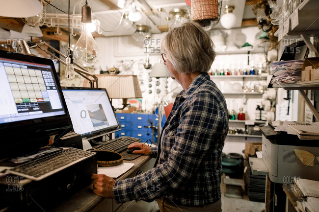 Side view of senior saleswoman using computer while standing at checkout in hardware store