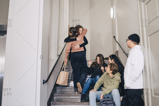 Teenagers looking female classmates embracing on steps at high school