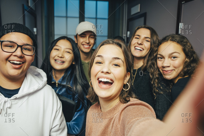 Cheerful teenage classmates taking selfie in corridor