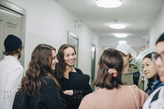 Teenage high school students talking while standing in corridor