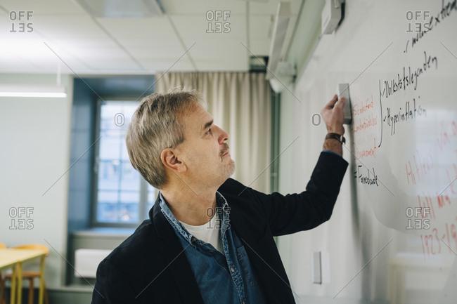 Male teacher erasing text on whiteboard
