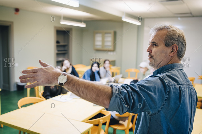 Senior male teacher gesturing while teaching during lesson in classroom