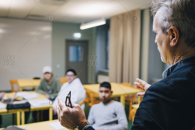 Male teacher gesturing while teaching students in classroom