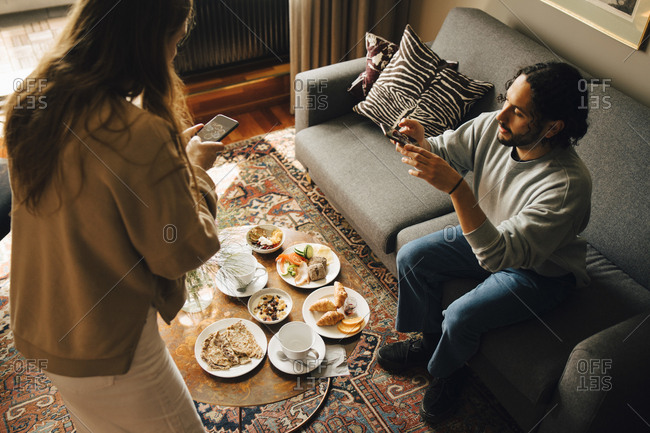 High angle view of couple photographing breakfast in hotel room