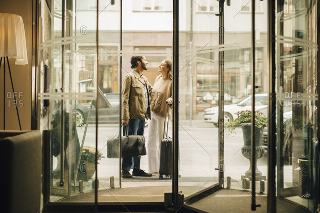 Couple with luggage talking while standing at doorway of hotel seen through glass