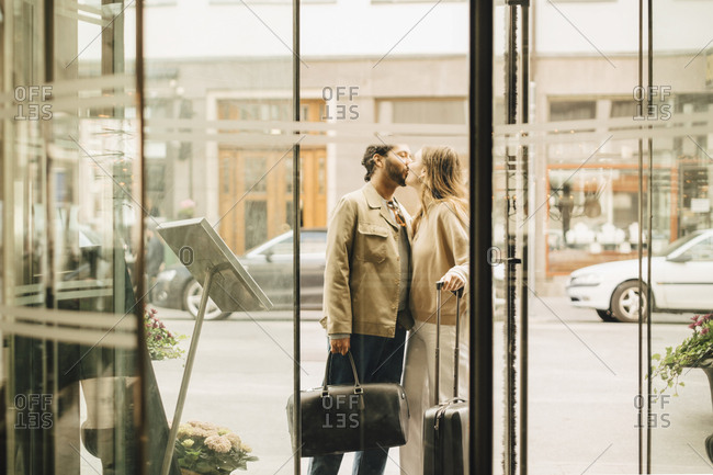 Couple with luggage kissing while standing at entrance of hotel