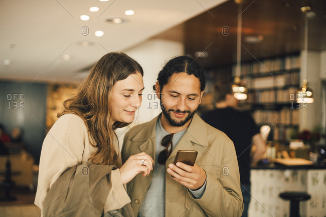 Couple using smart phone while standing in hotel