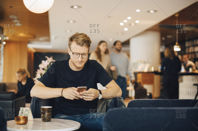 Mid adult man using smart phone while sitting in restaurant