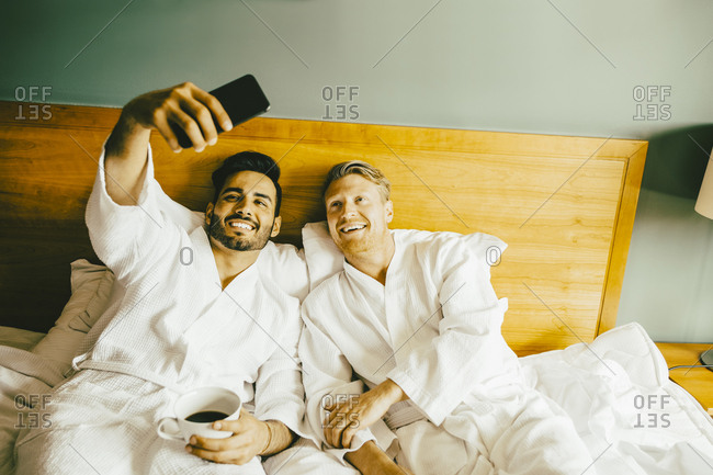 Smiling gay man holding coffee cup while taking selfie with boyfriend at hotel room
