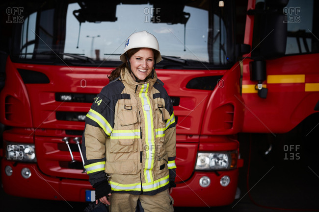 Portrait of smiling female firefighter standing in front of fire engine at fire station